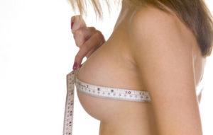 Жена, която измерва обиколката на гърдите си с шивашки метър